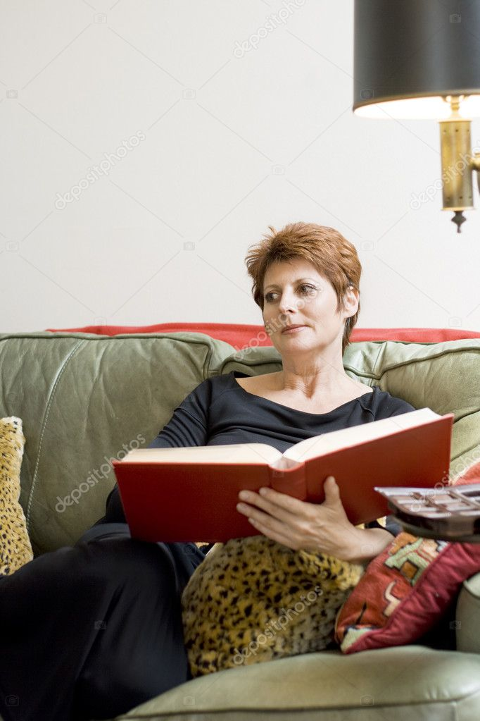 A beautiful mature woman is relaxing on the couch with a book.  Stock Photo #3000444