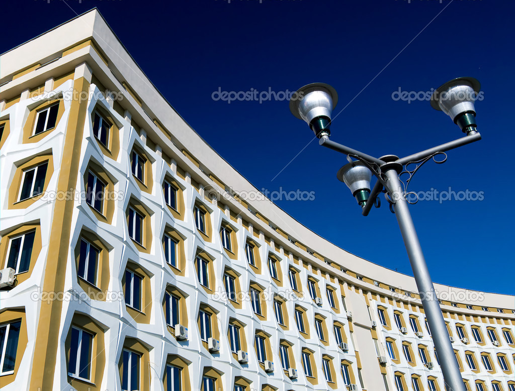 A street lamp contrasted with a modern building in the background — Stock Photo #2831648