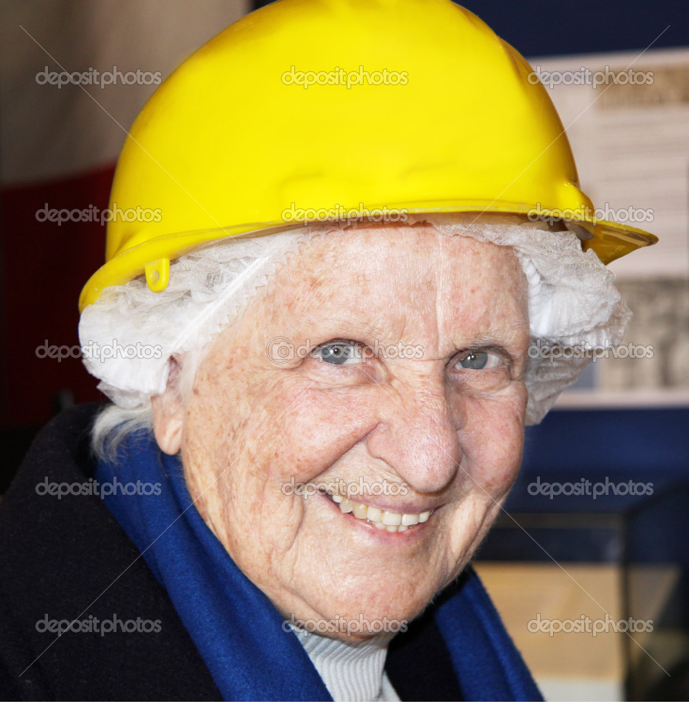Portrait of an old lady wearing a net and a hard construction hat just before taking a tour of war shelters for safety — Stock Photo #2965259
