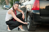Woman trying to change the wheel. — Stock Photo