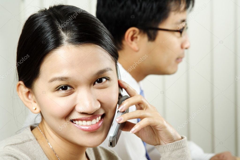 A businesswoman making a phone call with a businessman in the background — Stock Photo #3721835
