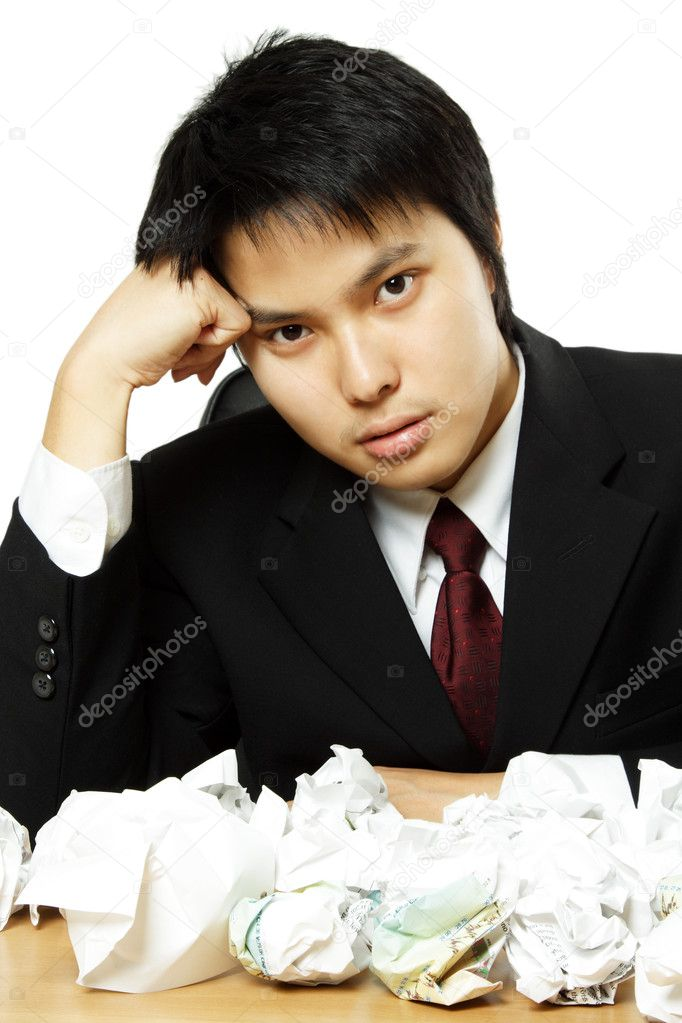 A stressed out businessman with crumpled paper all over table — Stock Photo #3748225