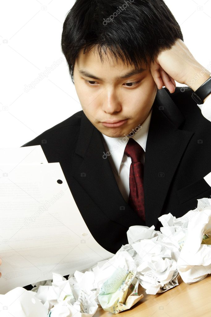 A stressed out businessman with crumpled paper all over table — Stock Photo #3748245