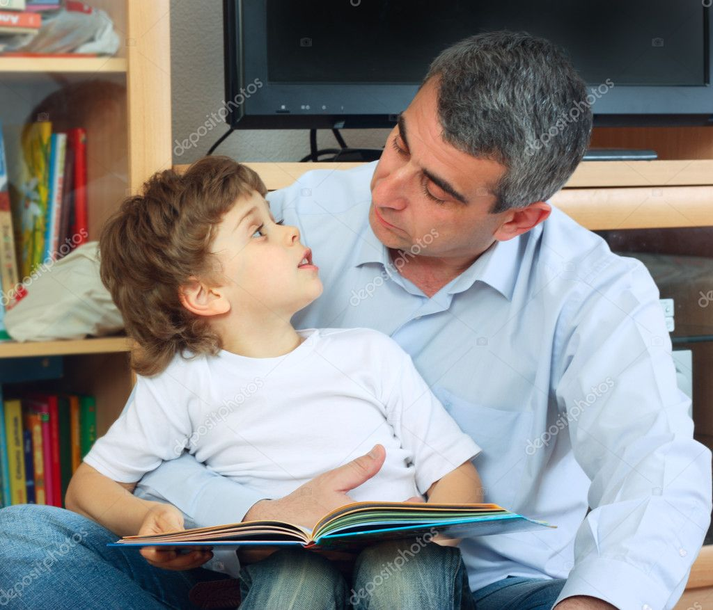 Man and little boy sitting on the floor in living room and reading book — Stock Photo #2754121