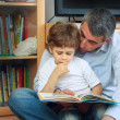 Man and little boy reading book - Stock Photo