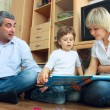 Man, woman and little boy reading book — Stock Photo #2831695