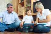 Man, woman and little boy reading book — Stock Photo