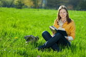 Girl with book on the grass — Foto Stock