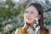 Young woman in blooming park — Stock Photo