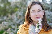 Jeune femme dans le parc fleuri — Photo
