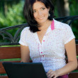 Girl with laptop in park — Stock Photo
