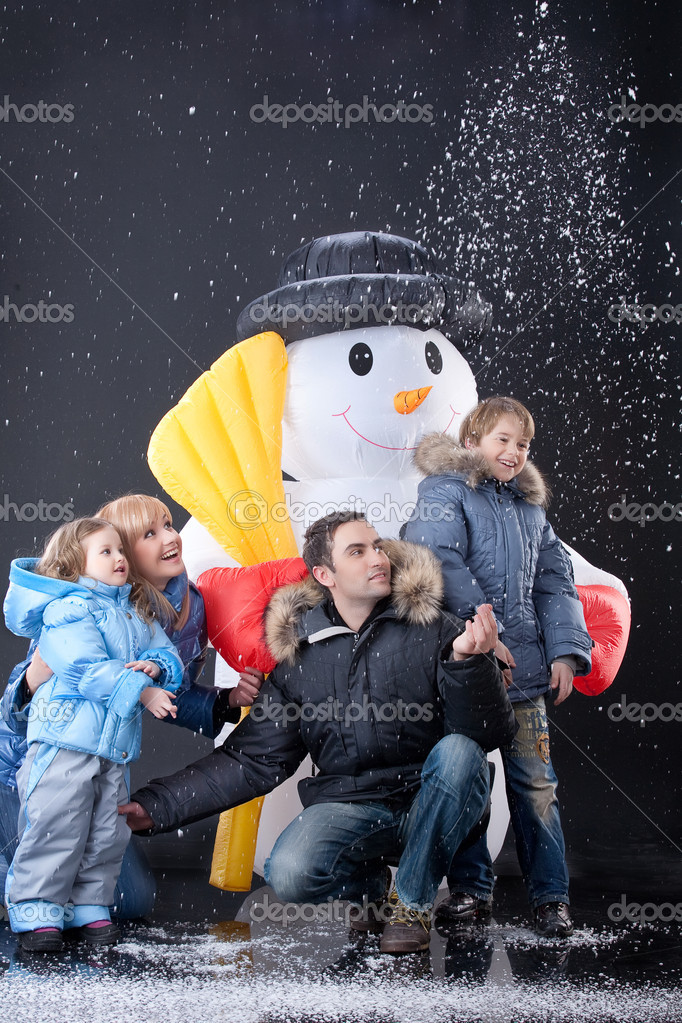 Young woman, man and children playing near the big snow doll  Stock Photo #2706272