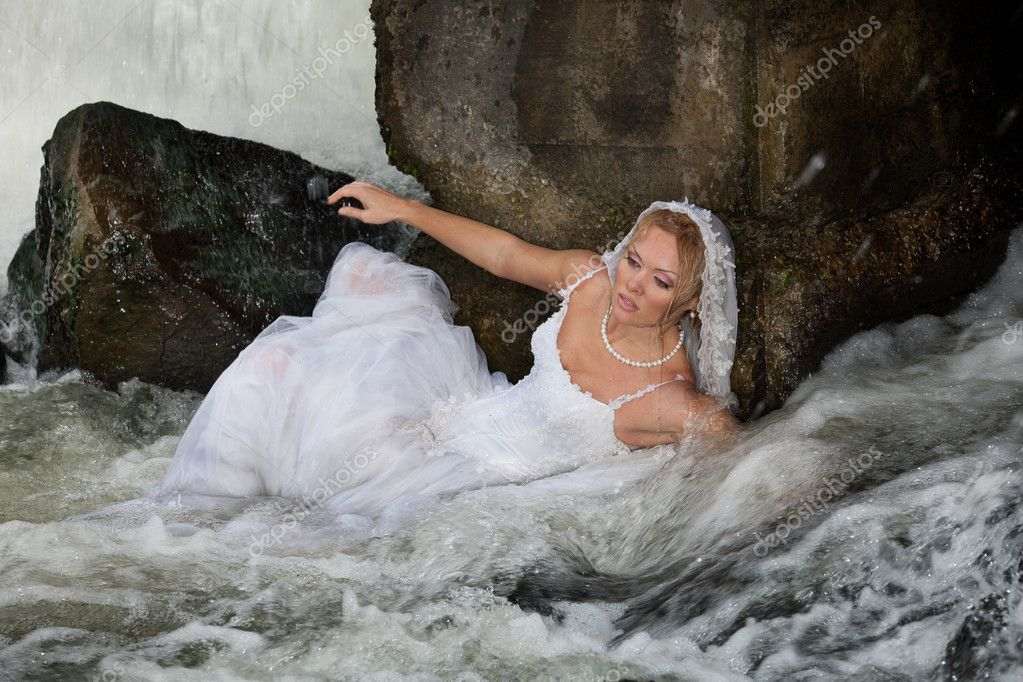 Young blonde woman in a white wedding dress near the waterfall — Stock Photo #3815381