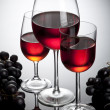 Three glasses of wine and cluster — Stock Photo