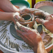 Potters' hands guiding woman's hands — Stockfoto