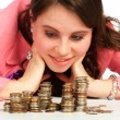 Stock Photo: Young womwatching stacks of coins