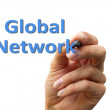 Hand writing the word global network — 图库照片
