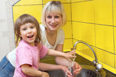 Mum washes to the child of a hand — Stock Photo