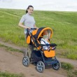 Mother takes baby in a stroller — Stock Photo