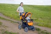 Matka ma dziecko w wózek — Zdjęcie stockowe
