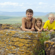 A woman with children on a rock — Stock Photo