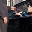 Car salesman giving the car keys to a young woman — Stock Photo