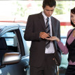 Portrait of young woman receiving car key from car salesman — Stock Photo