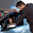 Car salesman standing outside new car while female customer sitting on it — Stockfoto