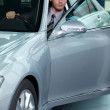 Car salesperson getting in car at showroom — Stock Photo