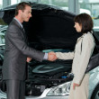 Car salesperson shaking hands with customer at showroom — Lizenzfreies Foto