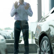 Young man curiously looking at new car in showroom — Foto de Stock