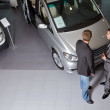 Car salesperson explaining car features to customer — Stock Photo #3808573