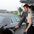 Young man opening door of car for woman - Stock Photo