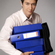 Young caucasian businessman holding a stack of binders — Stock Photo