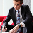 Young caucasian businessman sitting in modern office signing documents - Stock Photo
