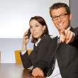 Portrait of businessman pointing while businesswoman using mobile phone — Stock Photo #3809283