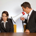 Businesswoman shouting at businessman through megaphone — Stock Photo