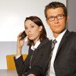 Portrait of businesswoman using mobile phone while businessman looking away — Stock Photo