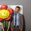 Businessman looking at balloon over woman's face - Stock Photo