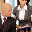 Royalty-Free Stock Photo: Young confident boss and his secretary looking on documents