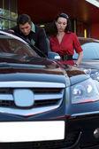 Giovane coppia guardando la nuova auto — Foto Stock
