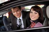 Retrato de um jovem casal que estava em um carro novo no showroom — Foto Stock