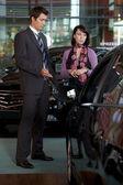 Car salesman explaining car features to customer — Stock Photo