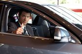 Portrait of man sitting in new car showing thumbs up — Stock Photo