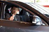 Retrato de um homem sentado no carro novo, mostrando os polegares — Foto Stock