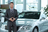 Portrait of car salesperson standing in car showroom — Stock Photo