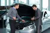 Car salesperson explaining about car's engine to customer — Stock Photo
