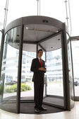 Young caucasian businessman at office revolving door with cellph — Stock Photo