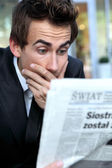 Young caucasian businessman reading bad news in newspapper — Stock Photo