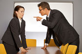 Businessman pointing towards businesswoman in office — Stock Photo